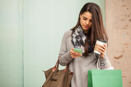 美しい若い女性彼女のスマート フォンを使用して、いくつかのモールでショッピングをしながらコーヒーを飲む