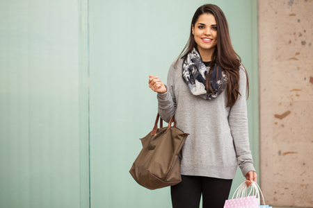 contact center: Pretty young woman carrying a purse and some shopping bags while visiting a shopping center