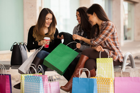 Three women taking a moment to show what the bought after a shopping spree at a mall