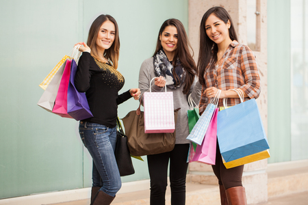 hispanic woman: Portrait of a group of three female Hispanic friends with too many shopping bags at the mall