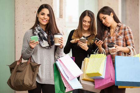 Group of young and spoiled housewives hanging out at a shopping mall and holding bags, coffee and smartphones