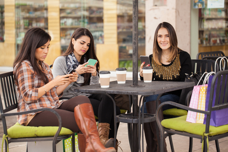 young group: Three young female friends drinking coffee at a restaurant and updating their social media status on their smartphones