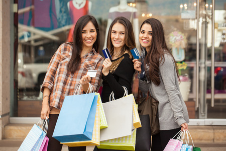 spending money: Portrait of a group of three young women spending money at a shopping center and showing their credit cards Stock Photo