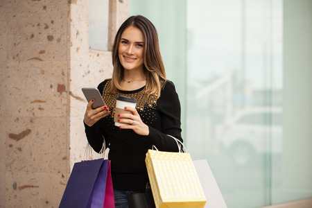Attractive young woman using her mobile phone at a shopping center and smiling. Lots of coffee space Imagens