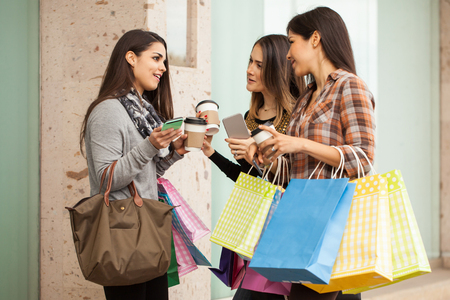 Group of three rich women carrying a lot of shopping bags and hanging out at a mall Imagens