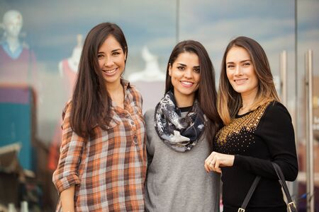 Portrait of a group of three female friends standing outside a clothing store in a shopping center Stock Photo