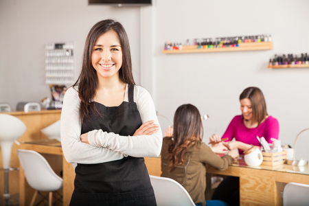 Precioso propietario de la empresa América femenina de pie frente a su salón de belleza, mientras que un cliente recibe una manicura Foto de archivo