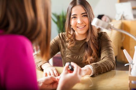 eye service: Portrait of a beautiful Hispanic brunette getting some nail polish at a beauty salon