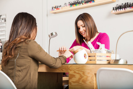 manicurist: Pretty Hispanic woman giving a manicure to a client at a nail salon Stock Photo
