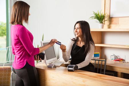 Vista de perfil de una mujer joven y bonita pagar con una tarjeta de crédito en una tienda