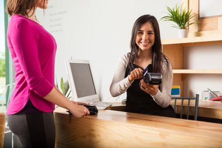 pagando: mujer joven latina linda que trabaja en una caja registradora y deslizar la tarjeta de crédito de un cliente