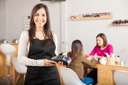 Ritratto di una giovane donna latina sveglia che tiene un terminale di carta di credito presso un salone di bellezza e sorridente