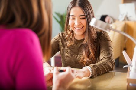 魅力的な若い女性リラックスしネイルサロンへの彼女の訪問を楽しんでいるとマニキュアを取得