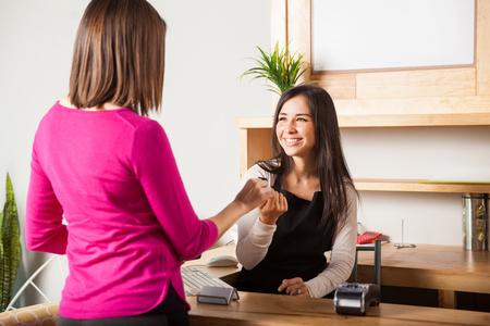 mujer trabajadora: Mujer joven linda en la caja registradora de tomar una tarjeta de crédito de la mano de un cliente y sonriente