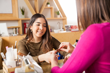 manicurist: Cute young woman enjoying her visit to a nail salon and getting her nails filed Stock Photo