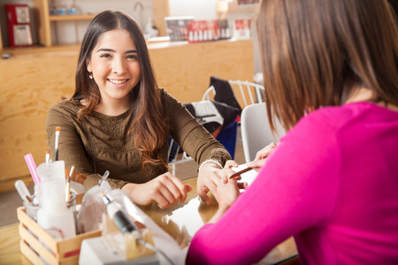 eye service: Portrait of a cute young brunette getting her nails done at a beauty salon and smiling Stock Photo