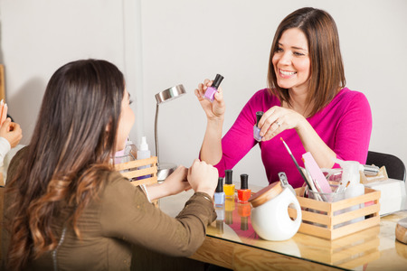 suggesting: Beautiful young woman working at a nail salon suggesting a nail polish color to one of her customers and smiling