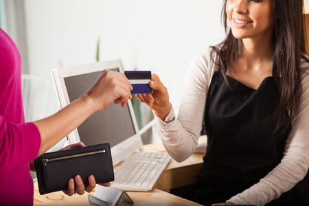 Close-up van een jonge vrouw die bij een kassa het nemen van een credit card van een klant