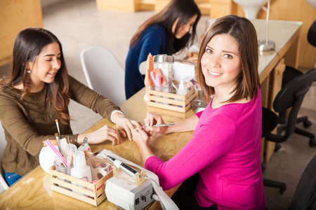 spa woman: Portrait of a cute Hispanic woman working in a nail salon and giving a manicure to one of her customers Stock Photo