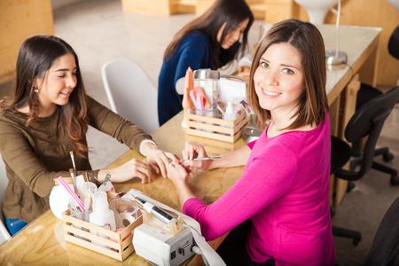 Portret van een leuke Spaanse vrouw die in een nagelsalon en het geven van een manicure tot een van haar klanten