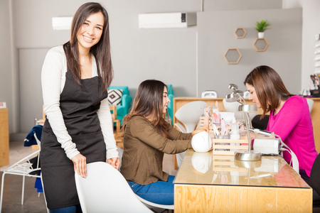 Portrait of a gorgeous young business owner inviting her customers to sit in a chair at her nail and beauty spa 版權商用圖片
