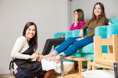 Portrait of a cute young woman working at a nail salon and giving a pedicure to a couple of women