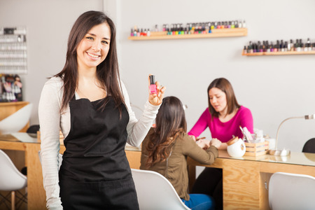 Attractive young brunette holding a nail polish bottel while standing in a nail salon