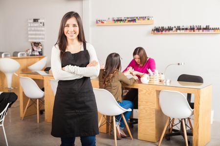 Portrait d'une belle jeune femme brune debout devant son salon de manucure et souriant