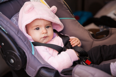 Pretty baby girl with a hat sitting on a child seat in a car ready for a ride with her parents