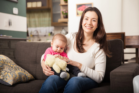 babysitter: Portrait of a cute babysitter taking care of a baby girl at home Stock Photo