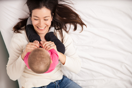 mum and daughter: High angle view of a gorgeous young mother playing and laughing with her baby girl on a bed