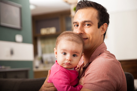 Attractive young single dad spending some time with his baby girl at home Imagens