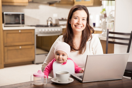 single mother: Pretty young Latin single mother working from home on a laptop computer while spending time with her baby daughter Stock Photo
