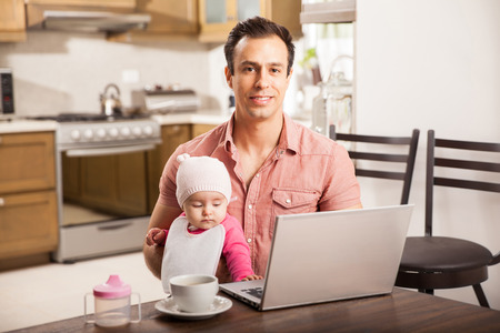 looking after: Portrait of an attractive young Hispanic father working on a laptop computer while looking after his baby daughter at home