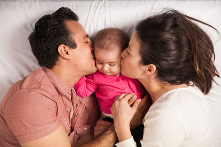 Couple of new parents lying in a bed with her baby girl and kissing her both at the same time Stock Photo