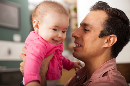 single father: Close portrait of a young single father holding his baby daughter at home