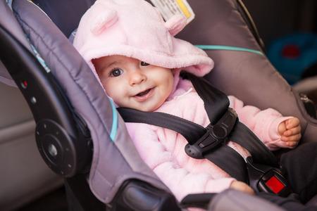 �infant: Retrato de una hermosa ni�a sentada en un asiento de coche y sonriente