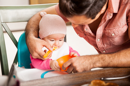 baby food: Beautiful baby girl being fed some soft food by her father at home