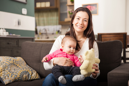 single: Cute young Hispanic brunette playing with her baby daughter and a teddy bear at home Stock Photo