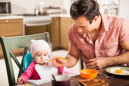 niña comiendo: Joven apuesto hombre comiendo el desayuno y alimenta a su bebé en casa