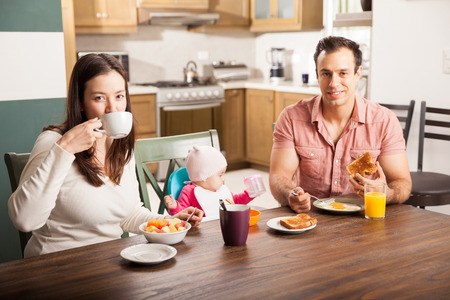 family eating: Portrait of a beautiful Hispanic family with a baby girl eating breakfast at home