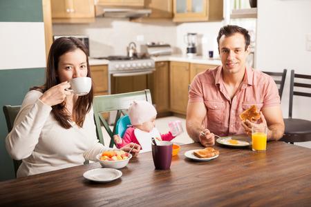 familia comiendo: Retrato de una hermosa familia hispana con una niña de desayunar en su casa