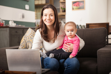 Portrait of a Hispanic young mother looking after her baby daughter and working on a laptop computer at home