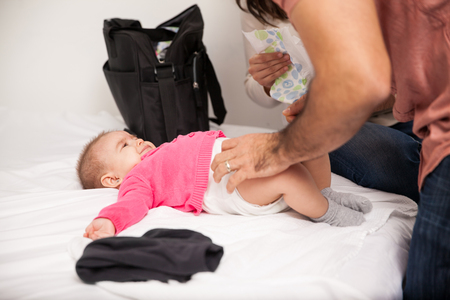changing clothes: Couple of parents working together to change their babys diaper at home