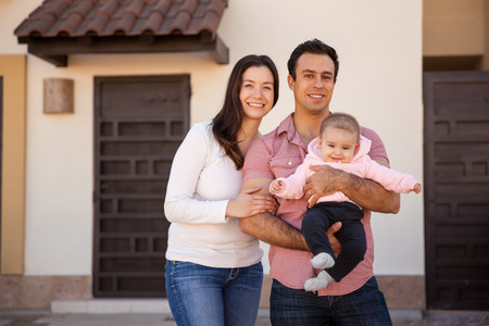 Portrait of an attractive Hispanic young couple and their baby girl standing in front of their new home and smiling Foto de archivo