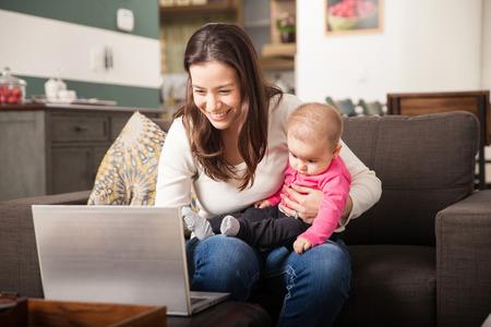Mujer joven linda que usa un ordenador portátil para el trabajo en casa cuidando de su bebé