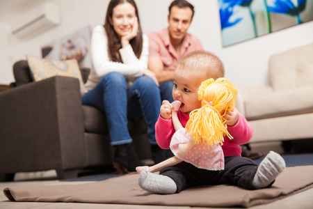 parents with baby: Couple of young parents watching their baby girl play with a doll at home