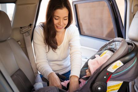 Hübscher Brunette, den Sicherheitsgurt eines Kinderautositz, bevor sie für eine Fahrt mit ihrem Baby Befestigung