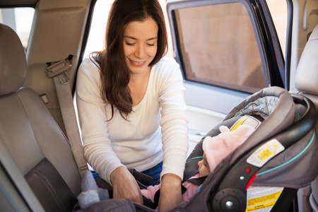 Pretty brunette fastening the seat belt of a child car seat before going for a ride with her baby
