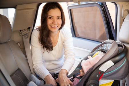 cinturon seguridad: Retrato de una madre joven magn�fica asegurar su beb� en un asiento para ni�os antes de conducir